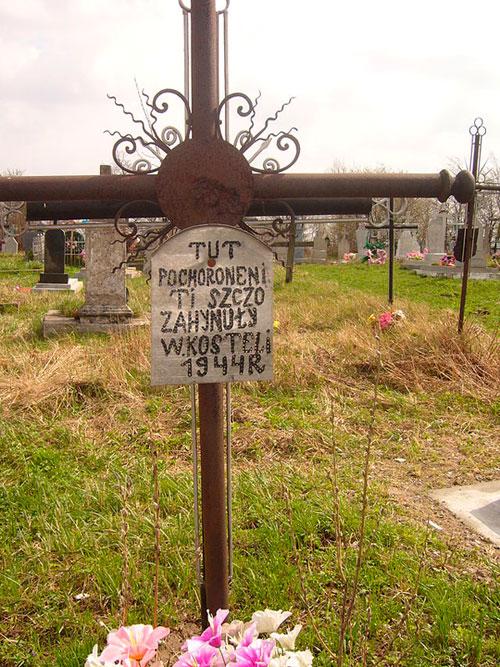 Крест на кладбище в Подкамене. Надпись на кресте сделана по-украински польскими буквами: «Здесь похоронены те, что погибли в костёле в 1944г.»